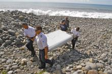 In this photo dated Wednesday, July 29, 2015, French police officers carry a piece of debris from a plane in Saint-Andre, Reunion Island. Air safety investigators, one of them a Boeing investigator, have identified the component as a flaperon from the trailing edge of a Boeing 777 wing, a U.S. official said. Flight 370, which disappeared March 8, 2014, with 239 people on board, is the only 777 known to be missing. (AP Photo/Lucas Marie)