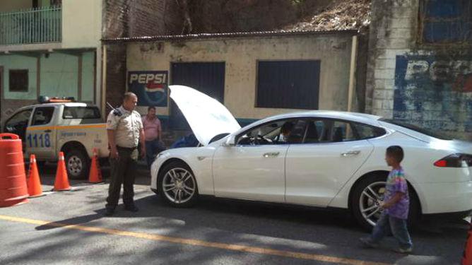 A Guatemalan border guards checks out the Tesla at the Guatemala-El Salvador Border.