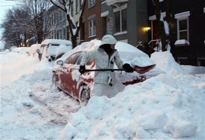 Liz Hall of Albany, N.Y., digs her car out of snow in the Center Square neighborhood on Friday in Albany.